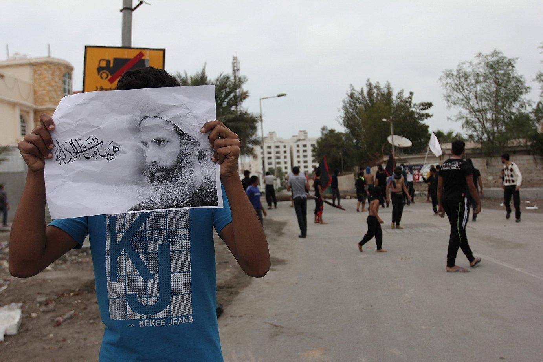 Herritar bat Al-Nimr klerikoaren argazkiarekin Bahraingo hiriburuan, atzo, Saudi Arabiako monarkiaren kontra izandako protestetan.