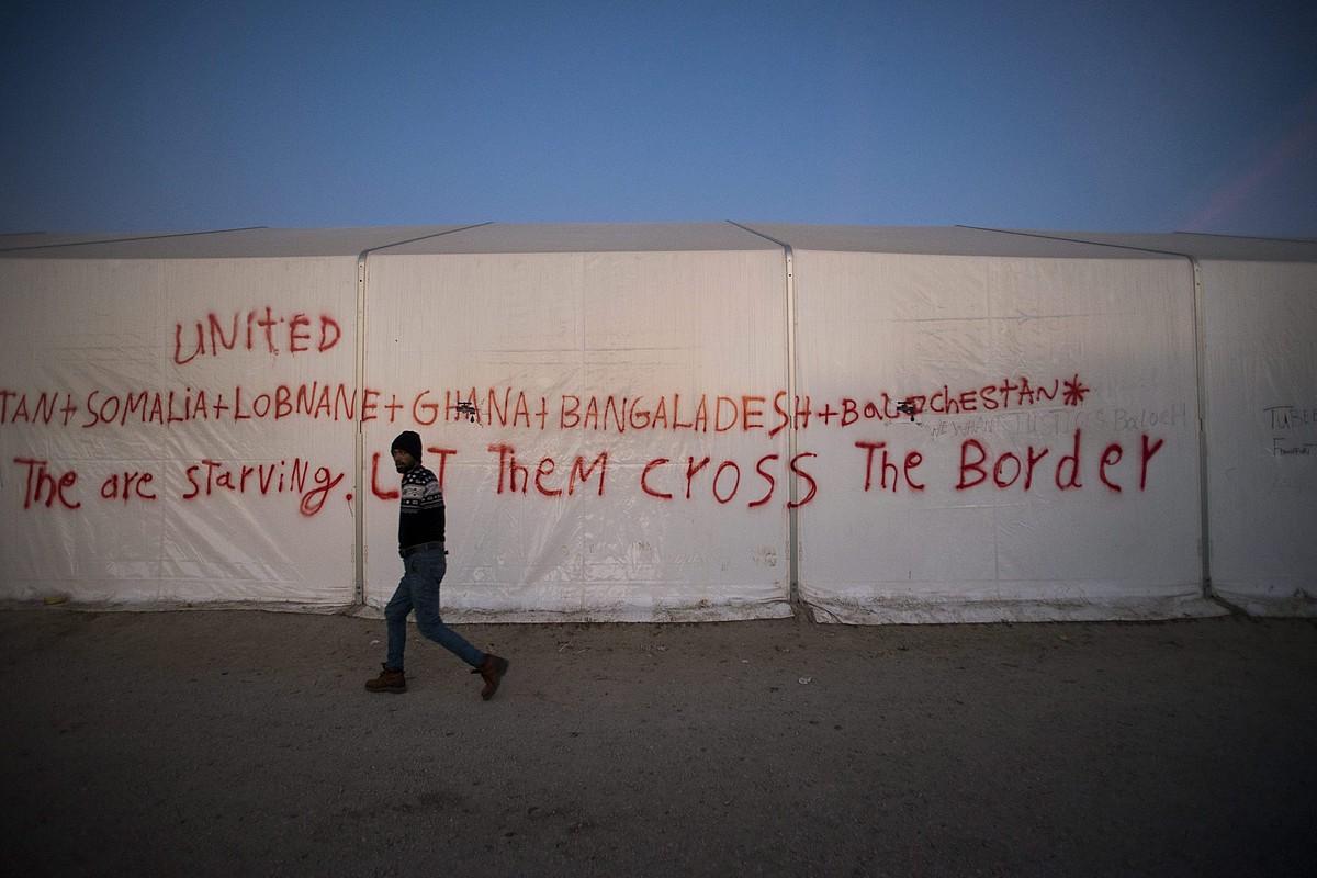 Errefuxiatu bat Idomenin, Greziaren eta Mazedoniaren arteko pasabidean, pintaketa baten aurretik igarotzen. ©ZOLTAN BALOGH / EFE