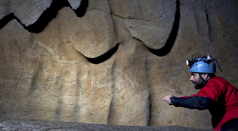 Diego Garate arkeologoa, pinturak seinalatzen. Bi zaldi antzeman daitezke, eta horietako batek <em>J.M.N.</em> hizkiak ditu gainean idatzita. ©BIZKAIKO FORU ALDUNDIA