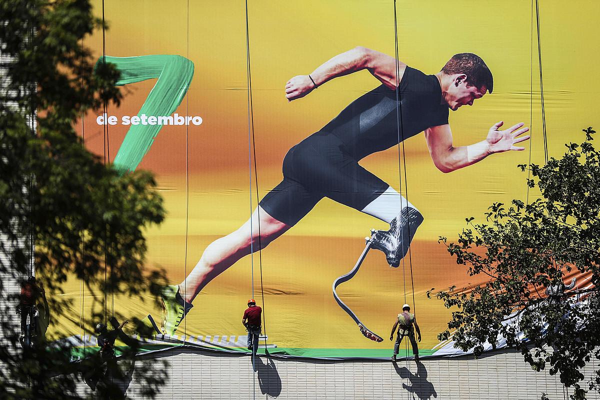 Bi langile, Rio de Janeiroko Paralinpiar Jokoak iragartzeko oihal erraldoi bat zabaltzen.