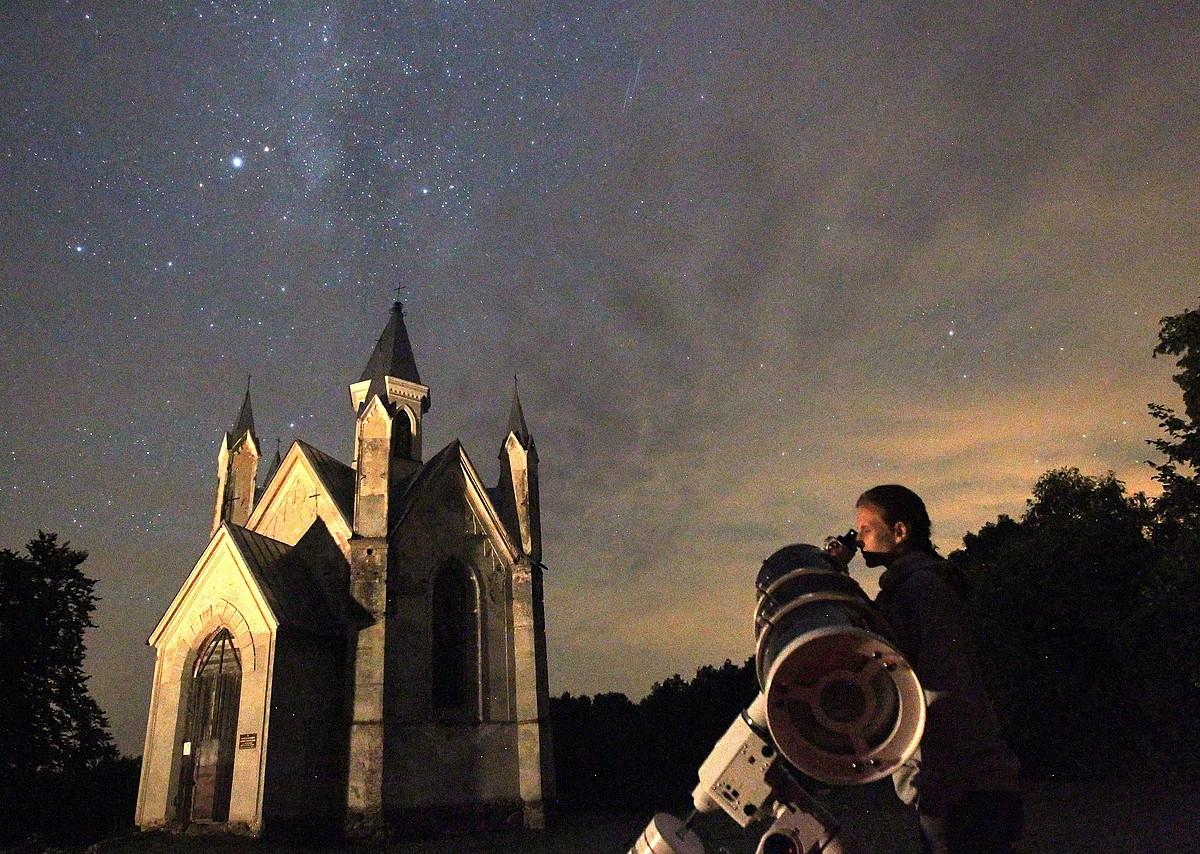 Pertsona bat, Bielorrusiako herritxo batean egindako artxiboko irudi batean, teleskopiotik begira izarrak aztertzen.