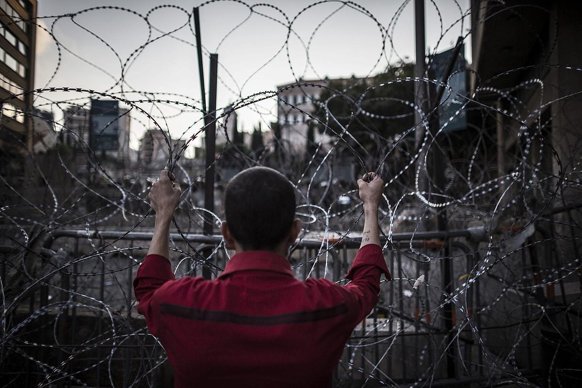 Herritar bat, Libanoko Gobernuaren egoitza inguratzen duen hesian, Beiruten. ©OLIVER WEIKEN / EFE