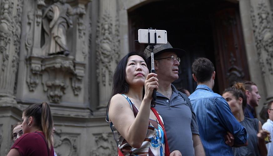Turista batzuk, Donostiako Parte Zaharrean, <em>selfie</em> makila klasikoarekin.
