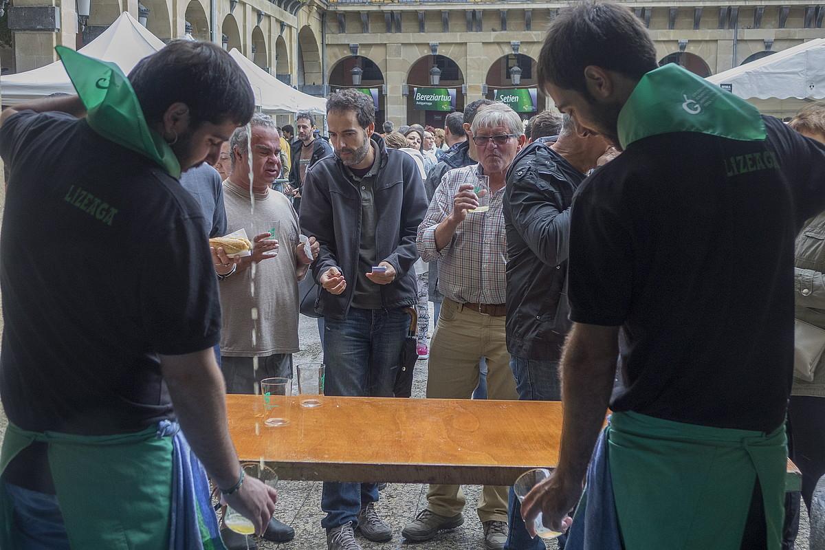 Sagardogileak bisitariei sagardoa ateratzen, Konstituzio plazako postuetako batean. ©ANDONI CANELLADA / ARGAZKI PRESS