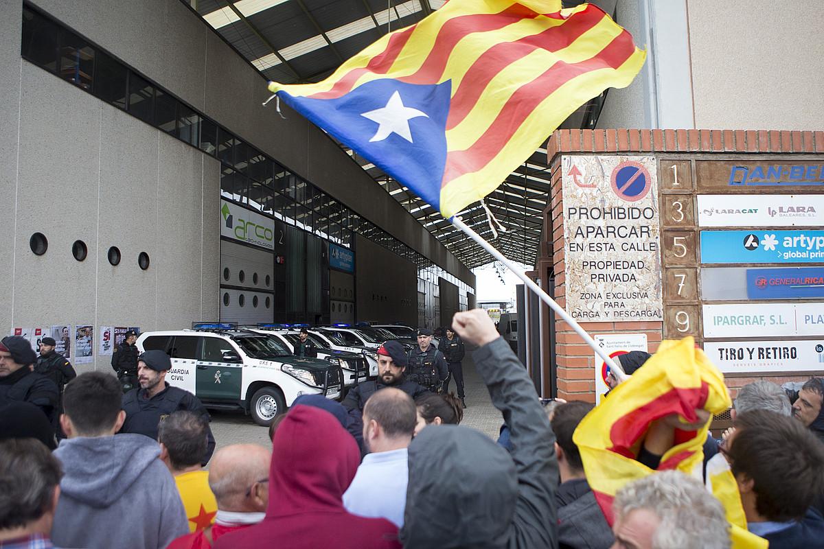 Jendea protesta egiten, atzo Guardia Zibilak Sant Feliu del Llobregaten miatu zuen inprentaren sarreran. / QUIQUE GARCIA / EFE
