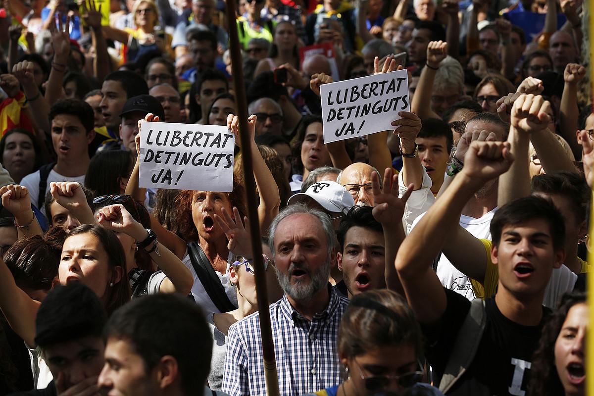 <em>Atxilotuak askatu!</em> mezuarekin afixak erakutsi zituzten hainbat manifestarik Justizia Auzitegi Nagusiaren parean. / ORIOL CLAVERA