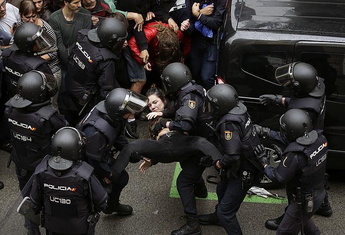 Bartzelonako Ramon Llull ikastetxera —ezkerrean— eta Gironan Carles Puigdemontek bozkatu behar zuen herrira Espainiako Poliziaren eta Guardia Zibilaren polizia asko joan zen. / A. EST�VEZ / A. DALMAU - EFE