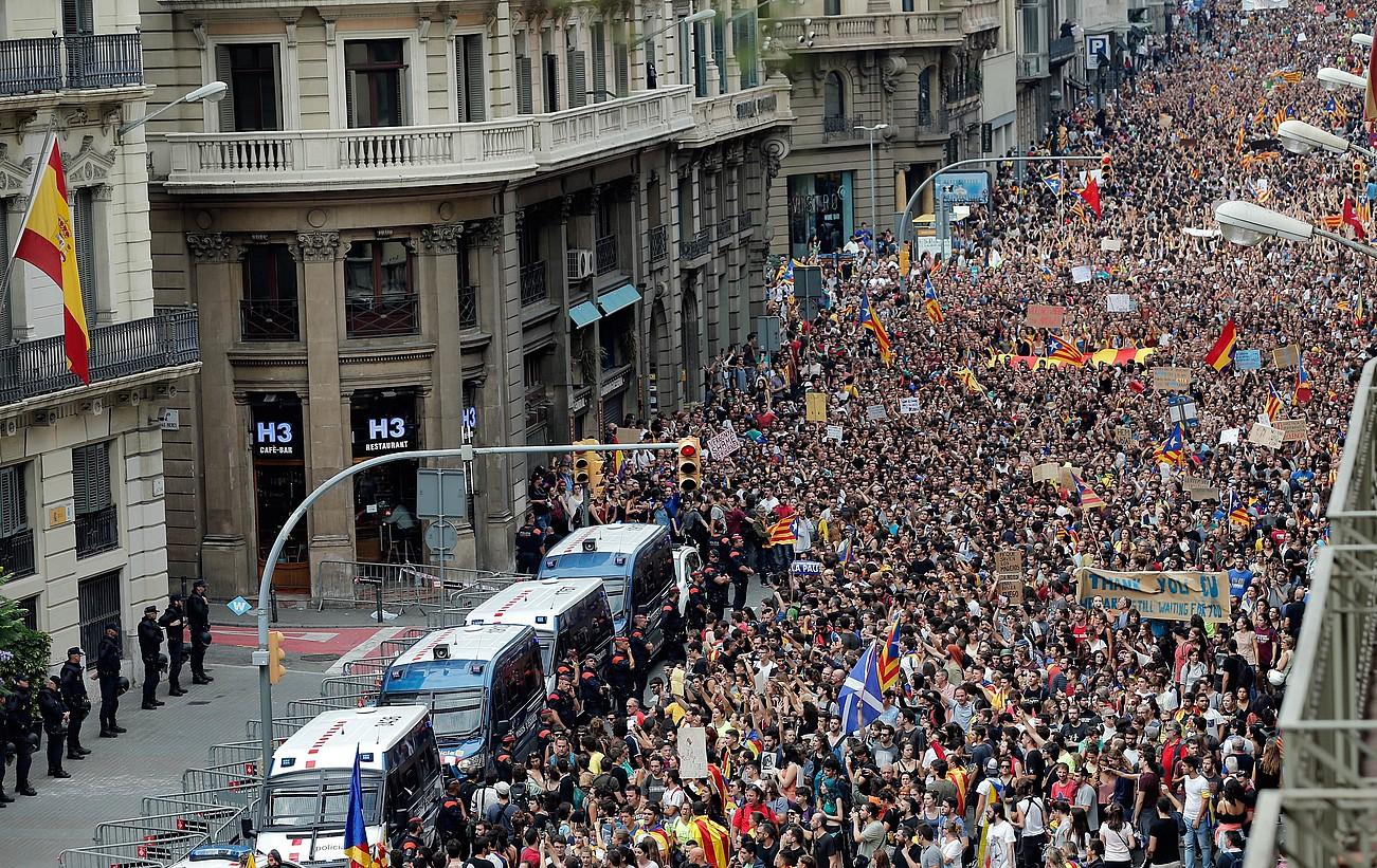 Hainbat manifestari Espainiako Poliziaren egoitza baten aurretik igarotzen, atzo, Bartzelonan, igandeko errepresioa salatzeko lanuztean. / JUAN CARLOS C�RDELNAS / EFE