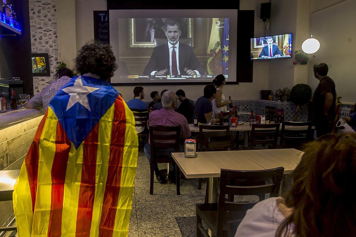Hainbat herritar Espainiako erregeak Kataluniari buruz zabaldutako mezua entzuten, herenegun iluntzean, taberna batean, Bartzelonan. / QUIQUE GARCIA / EFE