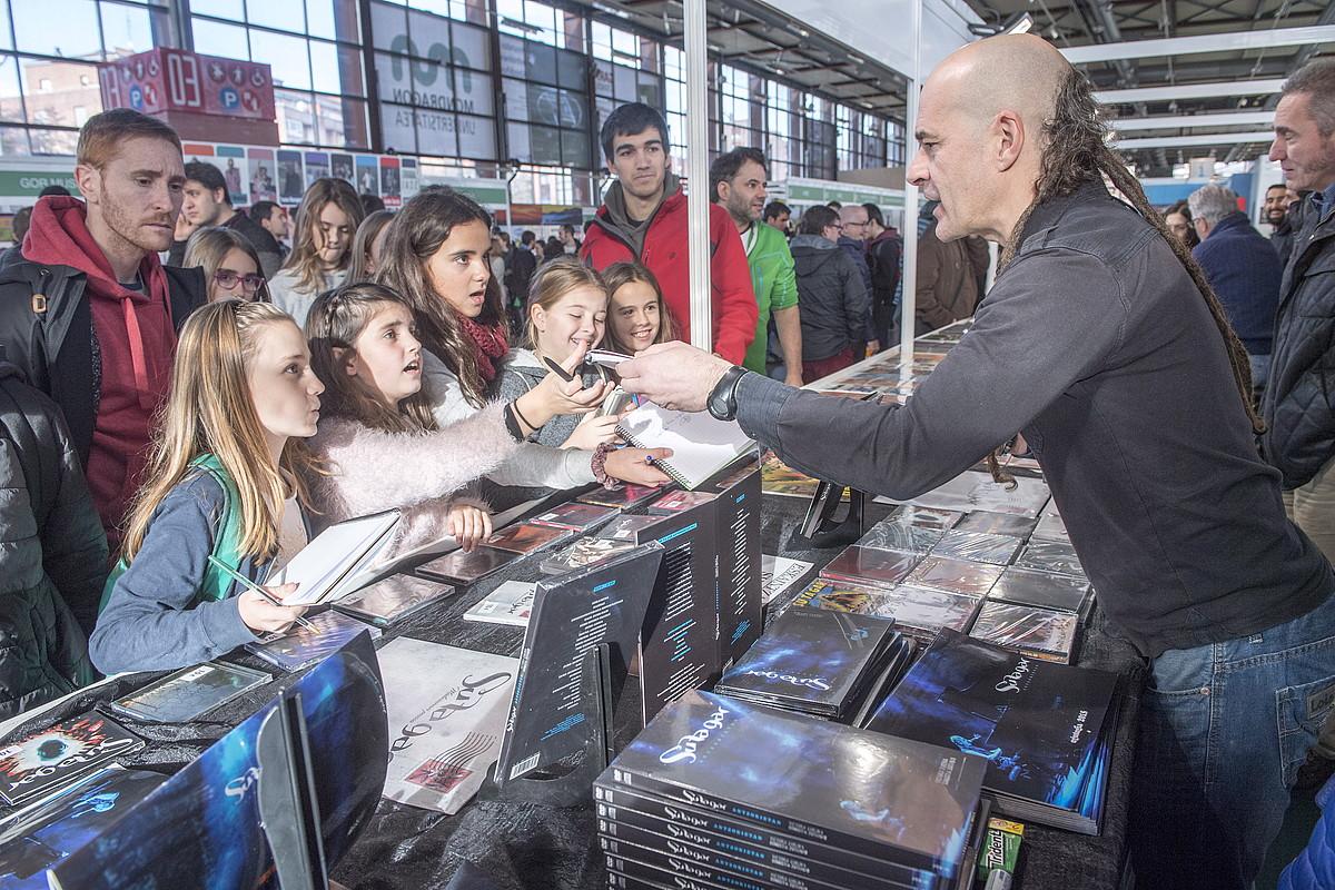 Xabi Bastida Su Ta Gar taldeko gitarrista, atzo, taldeak atera berri duen DVD-CDaren aleak azokan izan ziren gaztetxoei sinatzen. / JUANAN RUIZ / ARGAZKI PRESS