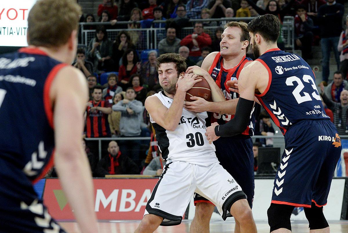 Baskoniako eta Bilbo Basketeko jokalariak, baloia eskurtzeko lehian, aurreko sasoiko derbian. ©RAMON GOMEZ / EFE