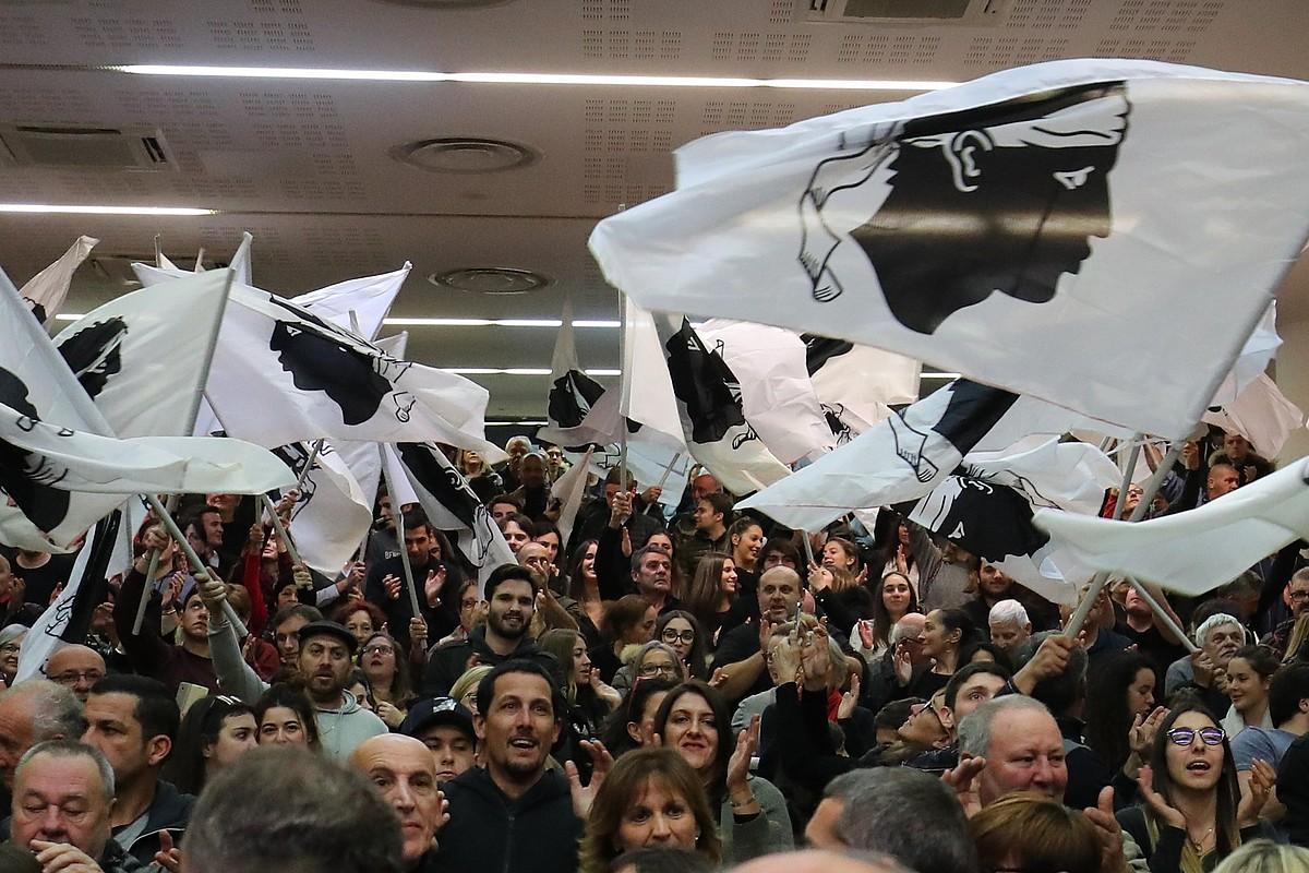 Jendea Korsikako banderak astintzen, hauteskunde kanpainako Pe A Corsica koalizioaren ekitaldi batean, azaroan.