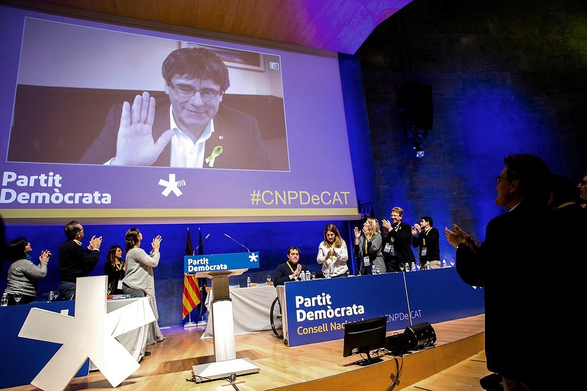 Puigdemont bideokoferentzian, atzo, PDeCATen Kontseilu Nazionalean. Eskuinean, Artur Mas txaloka. ©QUIQUE GARCIA / EFE