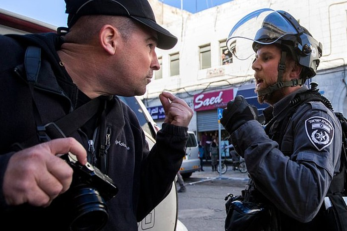 Israelgo polizia bat, kazetari bat kaletik bota nahian, abenduan, Jerusalemen gertaturiko istiluetan. ©JIM HOLLANDER / EPA / EFE