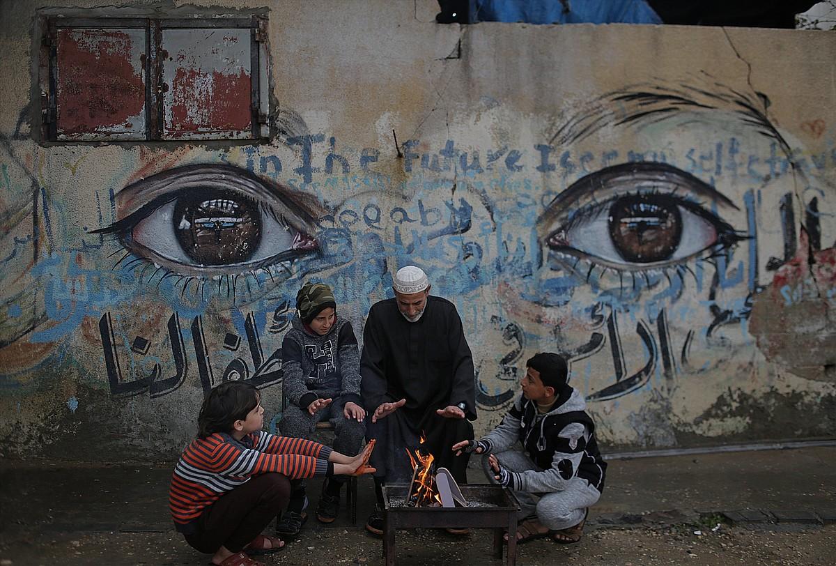 Familia palestinar bat joan den urtarrilean, eskuak berotzen, Beit Hanunen, Gazan.