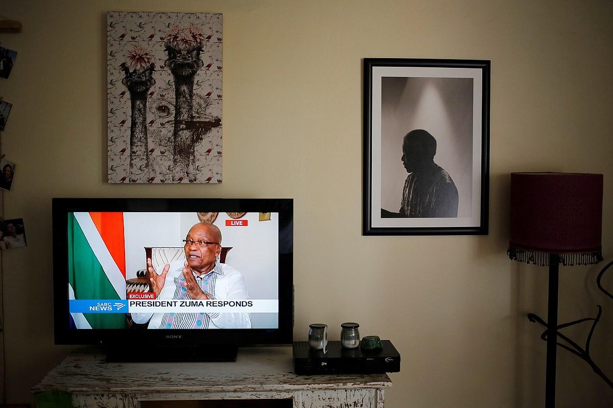 Pretoriako etxe batean ateratako irudi bat; Jacob Zuma, telebistako pantailan, eta Nelson Mandela hormako argazki batean. ©KIM LUDBROOK / EFE