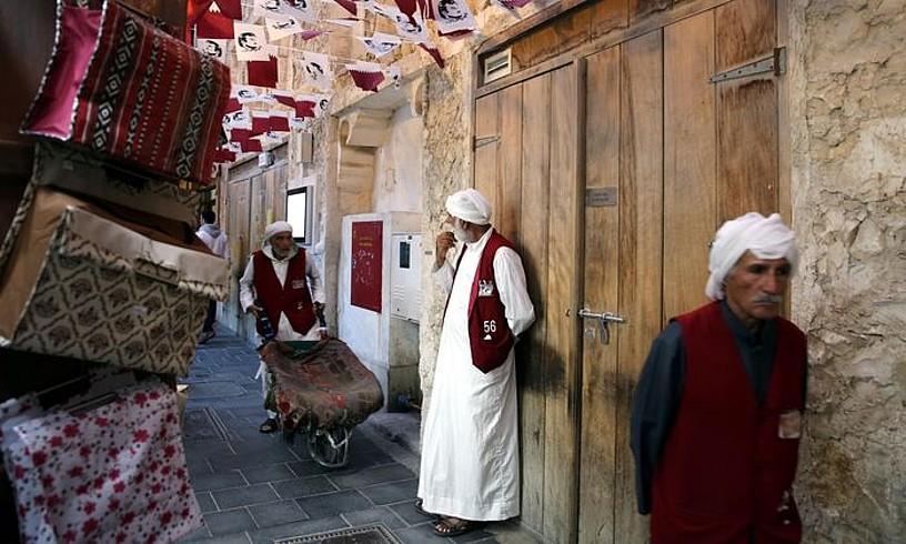 Qatarko banderak eta Al-Thani emirrarenirudiak Dohako Suq Waqif azokan, joan den urtarrilean. ©AMEL PAIN / EFE