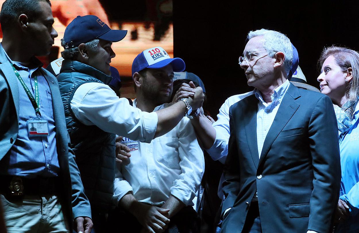Alvaro Uribe presidente ohia (eskuinean), haren alderdiko presidentegai Ivan Duqueri eskua ematea.