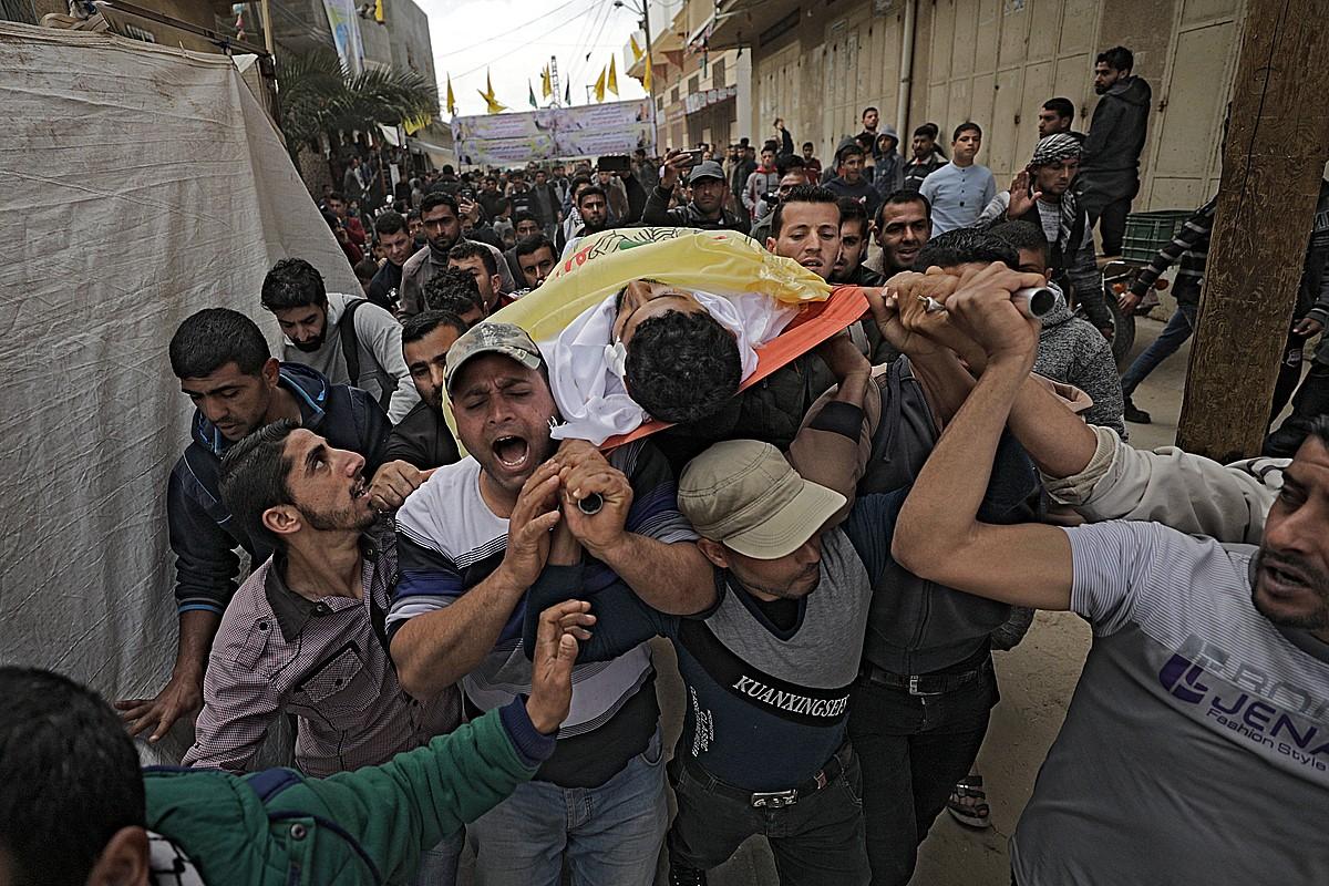 Palestinarrak Jihad Abu Jamous gaztearen gorpua eramaten, atzo, Gaza hirian. ©MOHAMEED SABER / EFE