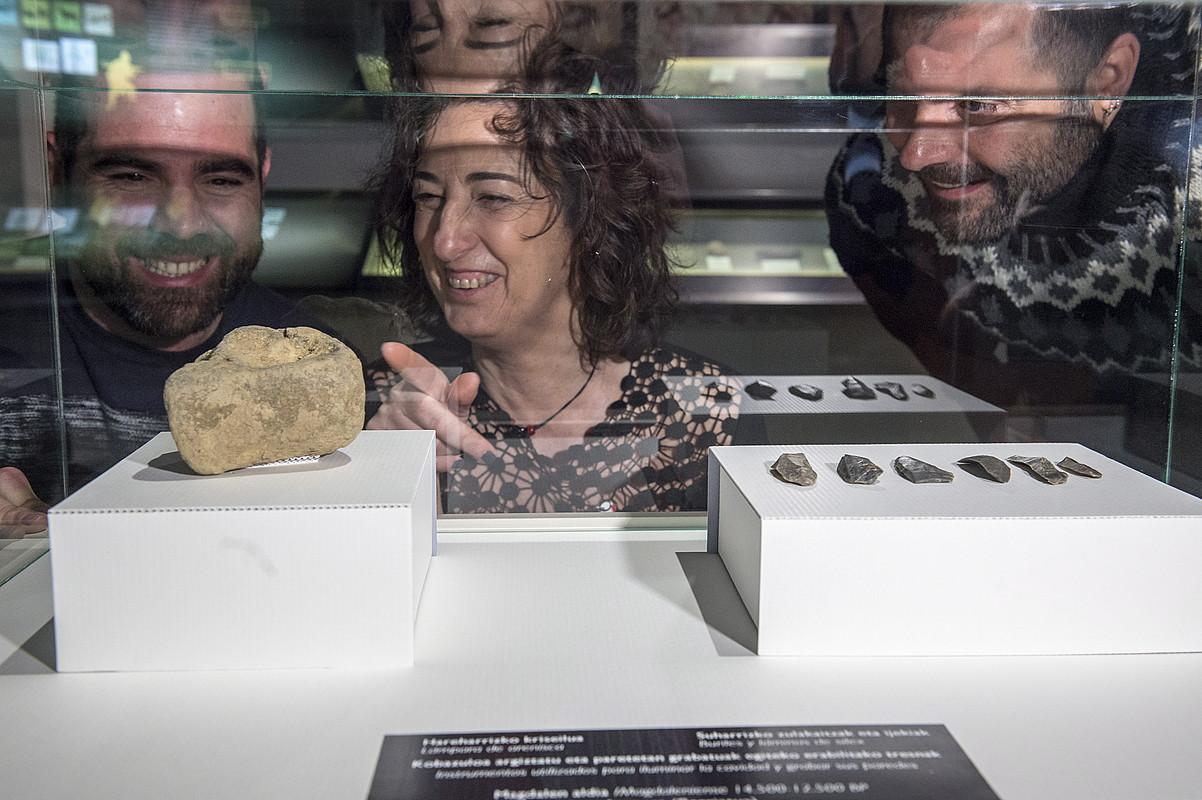Jon Arriola Berriatuko alkatea, Lorea Bilbao diputatua eta Diego Garate arkeologoa Atxurran, aurkitutako pieza batzuk ikusten.