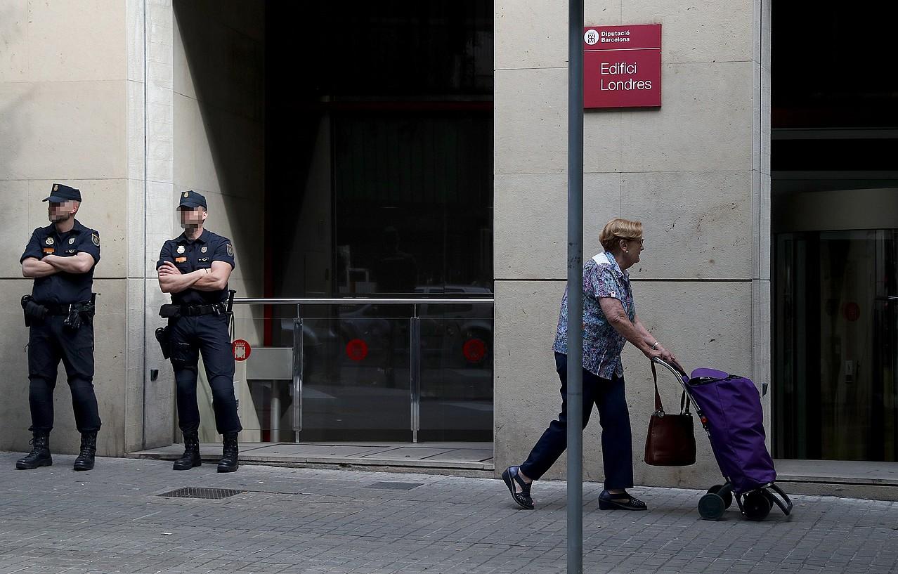 Espainiako Poliziako bi agente, Bartzelonako Diputazioaren egoitzaren sarreran, atzo, Bartzelonan. ©TONI ALBIR / EFE