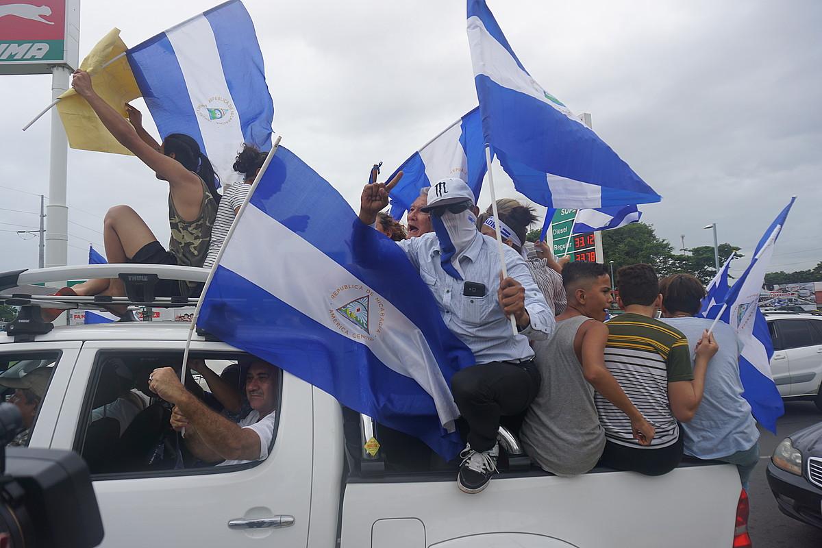 Hainbat lagun auto baten gainean asteon Managuan, Ortegaren aurkako manifestazio batean.
