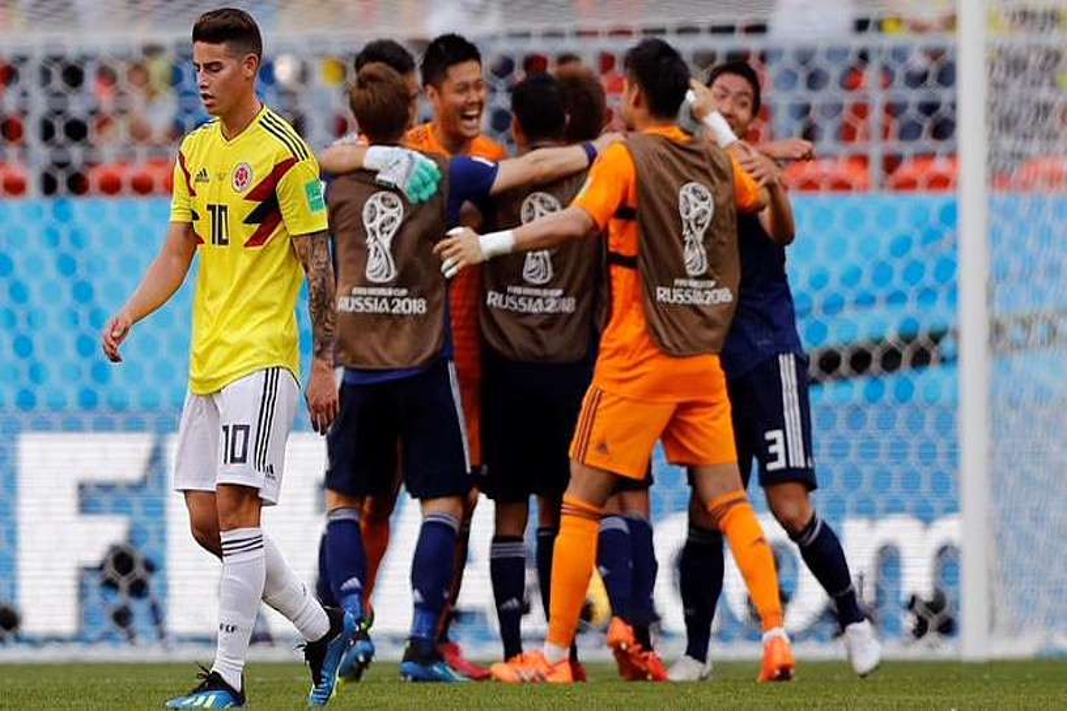James Rodriguez Kolonbiako jokalaria, burumakur, atzoko partidaren amaieran. Atzean, Japoniako jokalariak, irabazi dutela ospatzen.