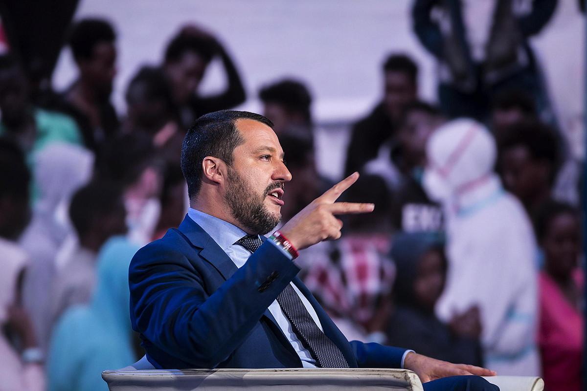Matteo Salvini Italiako Barne ministroa, herenegun, <em>Porta a Porta</em> saioan, atzean iheslarien irudiak dituela.