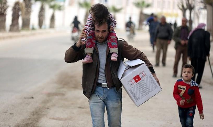 Herritar bat Turkiako Ilargi Gorriaren kaxa batekin Afrin hirian, martxoaren 19an, inbasioa gertatu eta bost egunera. ©AREF TAMMAWI / EFE