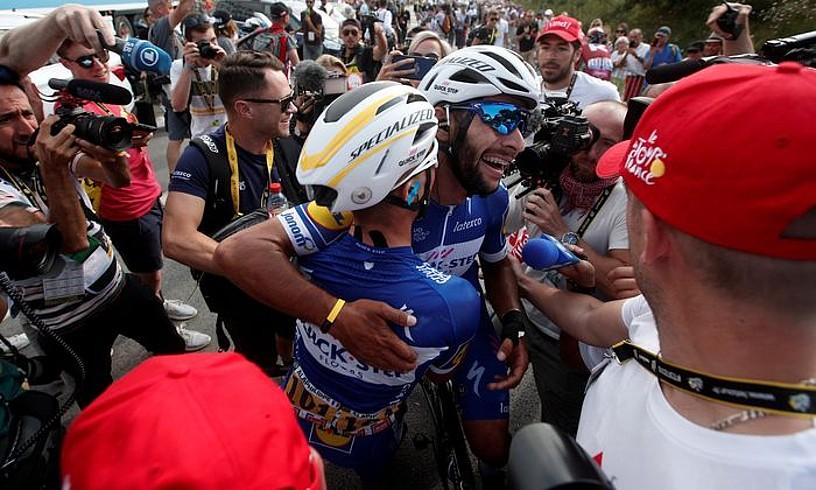 Fernando Gaviria eta Julian Alaphilippe Quick Step taldeko txirrindulariak elkar besarkatzen, atzoko etaparen ondoren. ©YOAN VALAT/ EFE