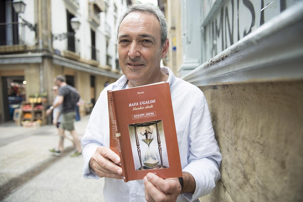 Rafa Ugalde, <em>Hondar aleak</em> bere lehen poema libura eskuetan, Donostiako Parte Zaharrean. &copy;JUAN CARLOS RUIZ / FOKU