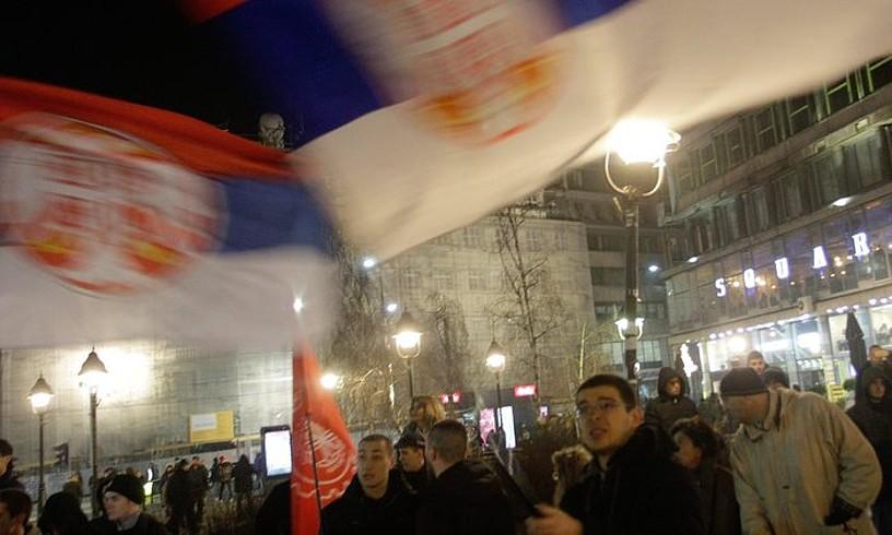 Hainbat lagun Serbiako banderak astintzen Belgraden, Kosovoren independentziaren hamargarren urteurrenaren harirako protesta batean.
