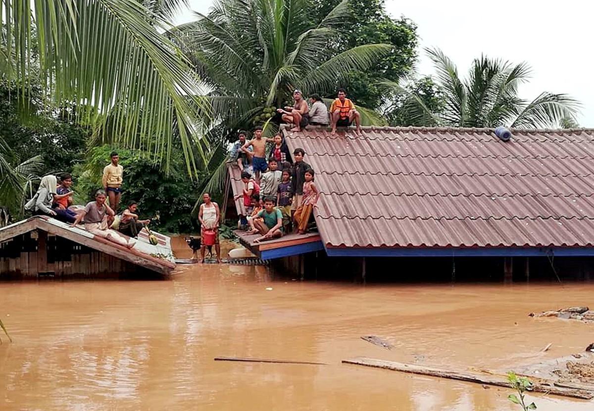 Hainbat pertsona teilatu gainean babes bila, atzo, Laosen.