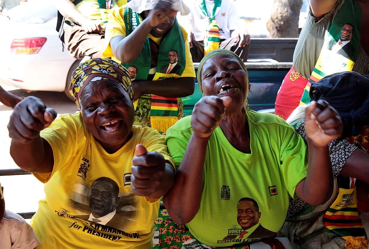 ZANU-PFko bi kide Mnangagwaren kamisetak soinean dituztela, hauteskundeetako emaitzak ospatzen, atzo. ©AARON UFUMELI / EFE