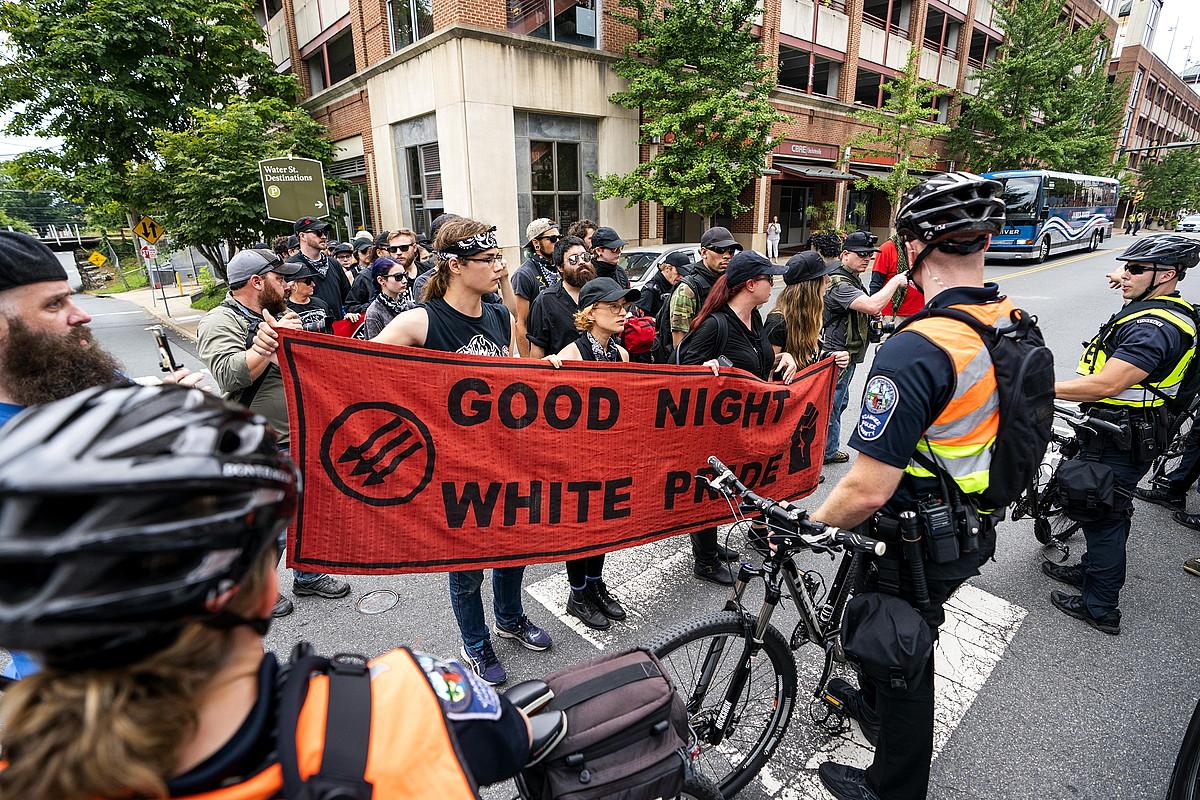 Antifaxista talde bat, poliziek osatutako hesi baten aurrean, atzo, Charlottesvillen.