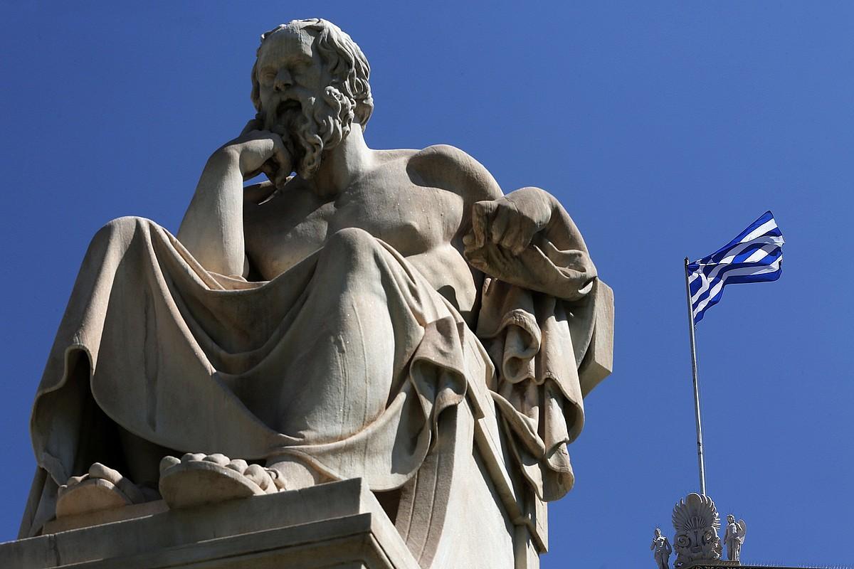 Greziako bandera bat, atzo, Atenasen, Sokrates filosofoaren estatua baten atzean. ©SIMELA PANTZARTZI / EFE