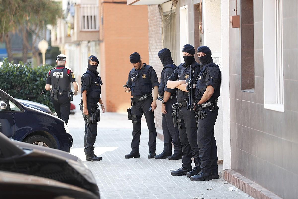 Mossoak, komisariari eraso egin dion gizonaren etxe ataria zaintzen, atzo, Cornella de Llobregaten.