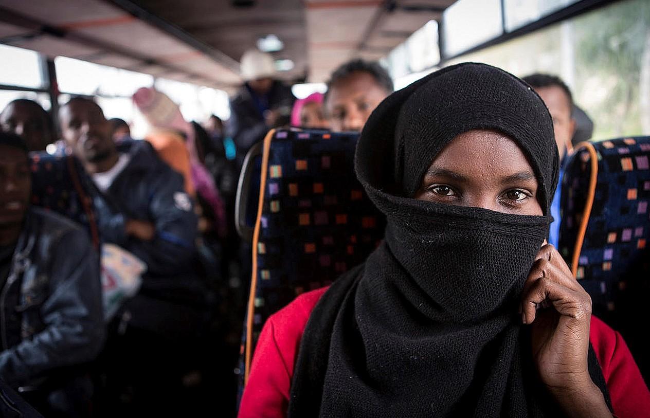 Neska eta mutil migratzaile adingabez betetako autobus bat, Lanpedusan (Italia).