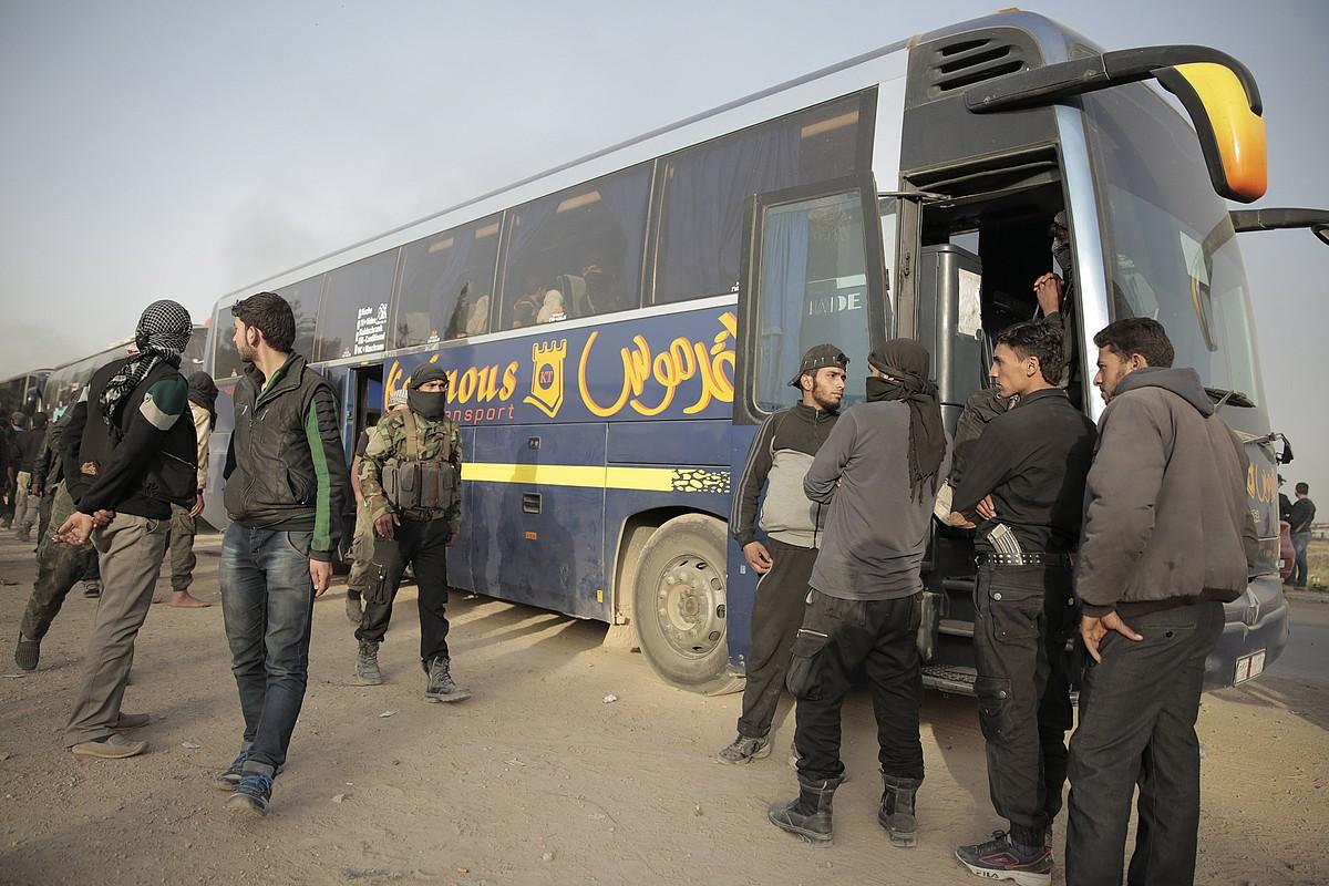 Matxino islamistak Damasko inguruan, iragan martxoan, gobernuaren autobusen alboan. Idlibera joan ziren. ©YOUSSEF BADAWI / EFE