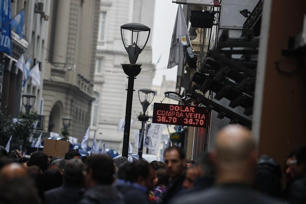 Dolarraren kotizazioa iragartzen duen kartela, atzo, funtzionario publikoen protesta baten ondoan. ©DAVID FERNANDEZ / EFE