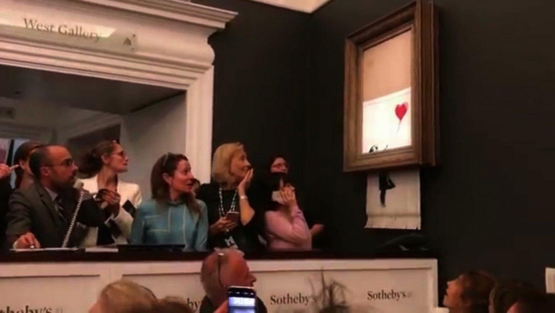 Jendea harriturik, Banksy artistaren <em>Girl With Balloon</em> obra hausten hasi zen momentuan, Londresko Sotheby's enkante etxean. Bideotik ateratako irudia. &copy;BERRIA