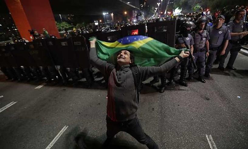 Bolsonaroren jarraitzaile bat garaipena ospatzen Sao Paulon, atzean Polizia Militarraren hainbat agente dituela. ©SEBASTIAO MOREIRA / EFE