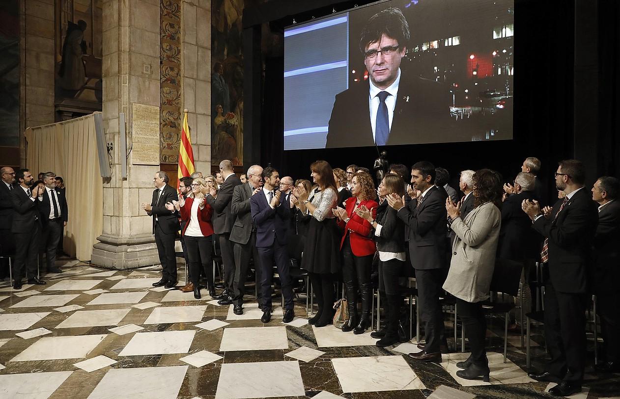 Carles Puigdemont, pantaila batean, eta, haren azpian, Generalitateko kideak txalo jotzen, atzo. ©ANDREU DALMAU / EFE