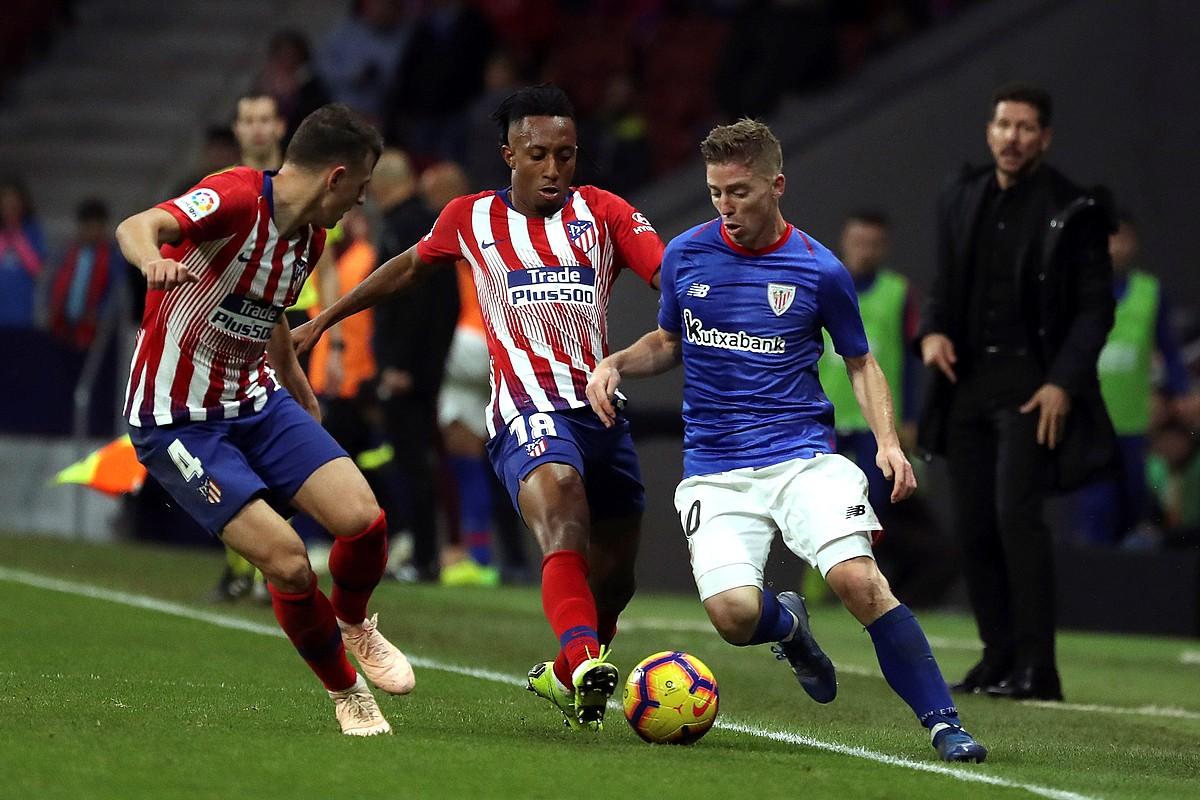 <b>Athleticeko Iker Muniain jokaldi bat egin nahirik, aurrean Atletico Madrileko Gelson Martins eta Santiago Arias dituela.</b> &copy;KIKO HUESCA / EFE