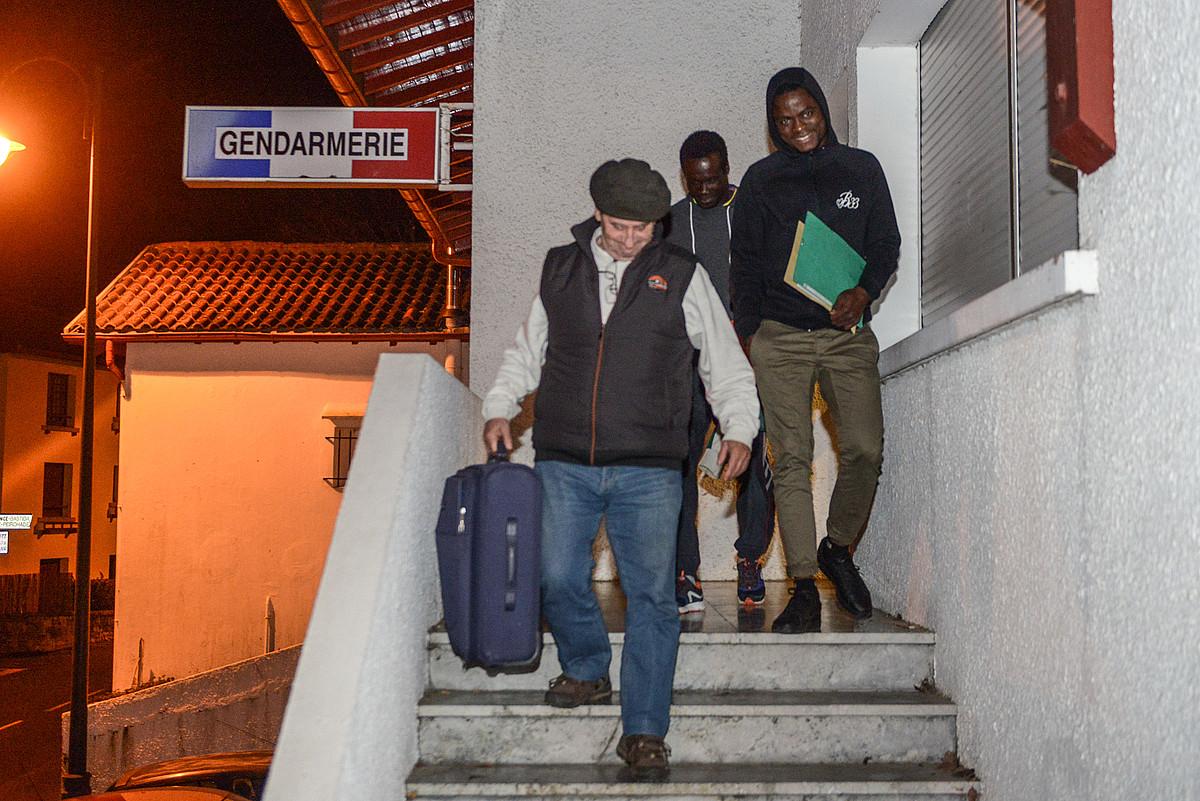 Bi migratzaileak, Xarlo Etxezaharreta aterpetzailearekin batera, atzo goizaldean, Jendarmeriaren egoitzatik irteten. ©ISABELLE MIQUELESTORENA