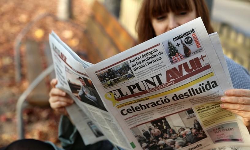 Emakume bat <em>El Punt-Avui</em> egunkaria irakurtzen, Gironan. &copy;QUIM PUIG / EL PUNT-AVUI
