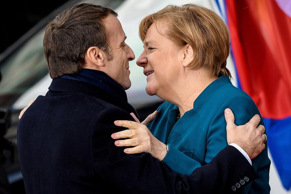 Macron Frantziako presidentea eta Merkel Alemaniako kantzilerra, elkar besarkatzen, atzo, Akisgrango Udaletxera sartu aurretik. ©SASCHA STEINBACH / EFE
