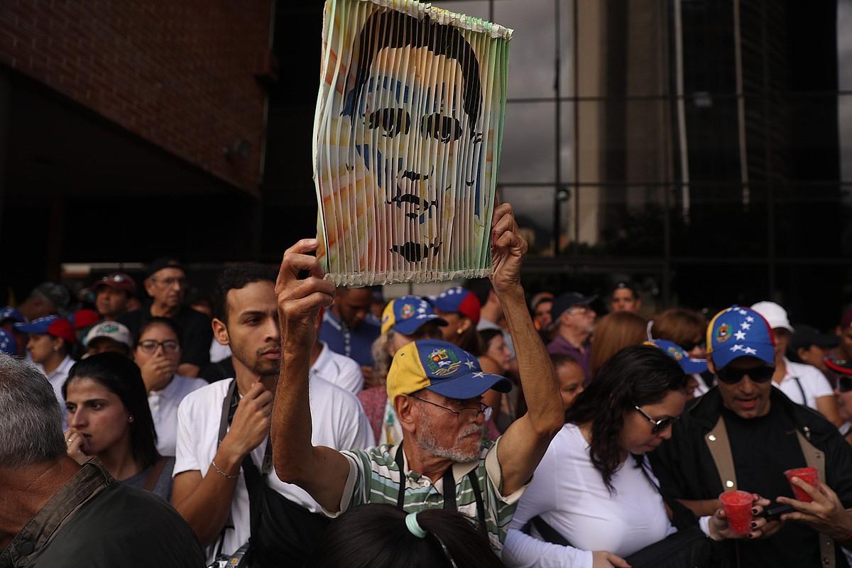 Herritar bat Juan Guaido oposizioko buruzagiaren irudiarekin, Caracasen. Milaka lagun elkartu ziren oposizioak deitutako manifestazioetara. ©MIGUEL GUTIERREZ / EFE