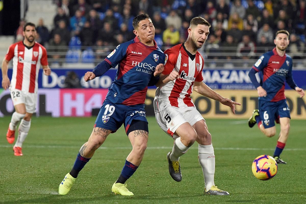 Chimy Avila Huescako jokalaria eta Yeray Alvarez Athleticekoa baloiarengatik lehian, atzoko partidako jokaldi batean.