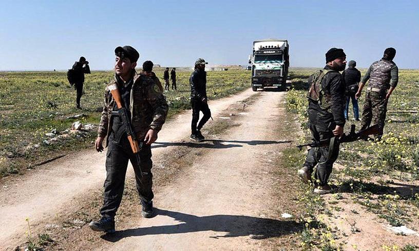 SDFko borrokalari batzuk, asteon, Baghuz inguruan. Atzean zibilak daramatzan kamioi bat dute. ©MURTAJA LATEEF / EFE